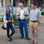 Two men and woman visiting during porch blessing dedication