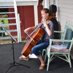 Cellist playing on Bird-Werner porch during porch blessing dedication