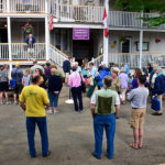 people visitng with each other in front of Bird-Werner and Shaw houses during porch blessing dedication