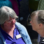 Mary Knepp having a conversation with woman during porch blessing dedication